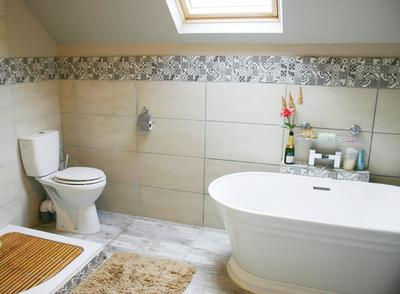 lucury bathroom with oversize rainwater sower, double vanit, loo and free-standing plunge bath